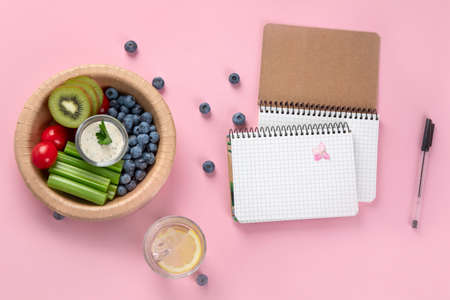 Healthy vegetarian lunch. Berries, fruits and vegetables. Healthy concept with nutrition food. Office desk table with spiral notebook. Top view, flat lay