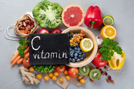 Foods high in vitamin C. Food rich in antioxidant, fiber, carbohydrates. Boost immune system and brain; balances cholesterol; promotes healthy heart. Top view, copy space, with chalkboard
