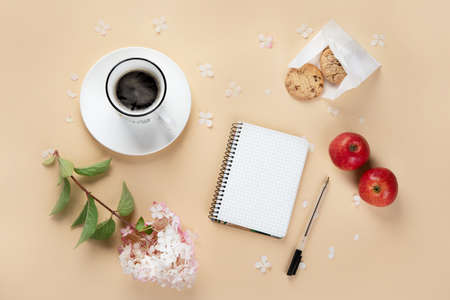 Morning cup of coffee, empty notebook, snacks and hydrangea flowers. Top view, flat lay.