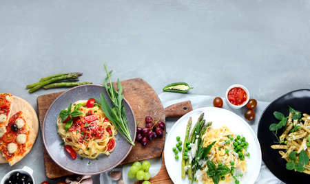 Variety of homemade prepared vegan pasta, pizza and snacks on gray background. Italian cuisine. Top view, flat lay with copyspace. 版權商用圖片