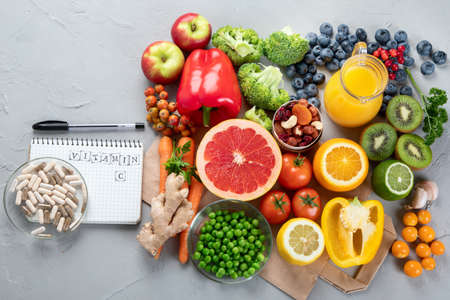 Foods high in vitamin C. Food rich in antioxidant, fiber, carbohydrates. Boost immune system and brain; balances cholesterol; promotes healthy heart. Top view, copy space, with chalkboard, with empty notebook Foto de archivo
