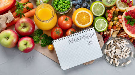 Foods high in vitamin C. Food rich in antioxidant, fiber, carbohydrates. Boost immune system and brain; balances cholesterol; promotes healthy heart. Top view, copy space, with notebook Foto de archivo