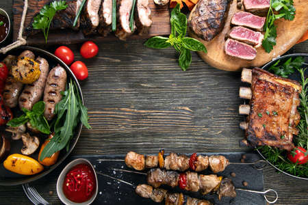Assorted grilled meat with vegetables on wooden background. Barbecue menu. Top view, copy space. Standard-Bild