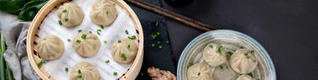 Chinese steamed buns served with dipping sauce and fresh vegetables. Top view, Copy space, panorama, banner