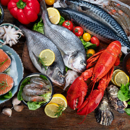 Fresh fish and seafood with herbs, spices and vegetables on rustic wooden background. Balanced diet and cooking concept. Healthy eating. Top view