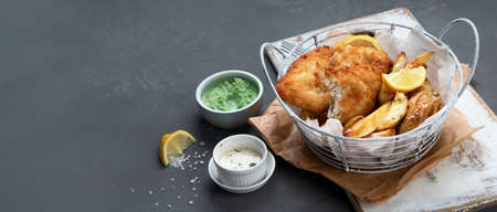 British traditional cuisine fish and chips. Served with mashed peas and different sauces. Copy space. Imagens