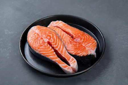 Fresh raw salmon steaks with herbs and oil. Ingredients for cooking.