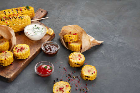 Sweet corn cobs on board grilled with pepper with souce added. Sliced corn in paper bags. Copy space