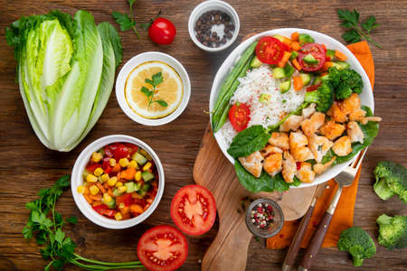 Delicious healthy homemade chicken and rice diner with fresh vegetables on wooden background. Top view Archivio Fotografico