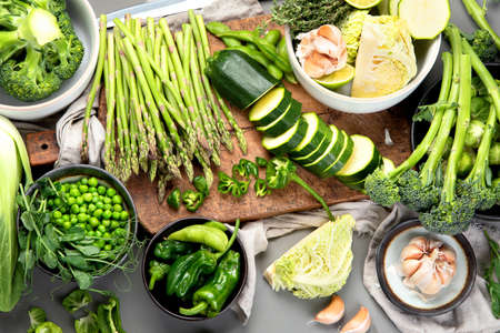 Set of various green vegetables and fruits like cabbage, broccoli, asparagus, peas, Brussels sprouts, zucchini, peppers, garlic, beans, pak choy, lime, apple. Healthy and nutricious vegetarian meal. Source of proteins and cellulose. Top view