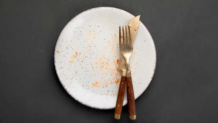 Pile of empty and dirty plates with food leftovers on dark background. Top view, copy space