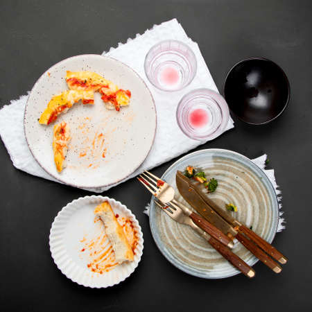 Pile of empty and dirty plates with food leftovers on dark background. Top view, copy space Stock Photo