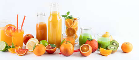 Raw fresh citrus juices and fruints in glasses and bottles on white background