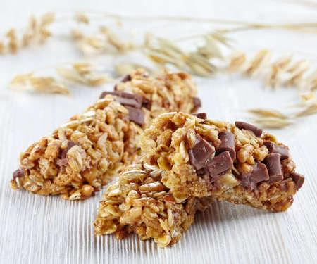 barra de cereal: Barras de granola con chocolate en el fondo de madera blanca