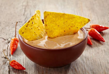 corn chip: Bowl of dip and nachos on wooden background