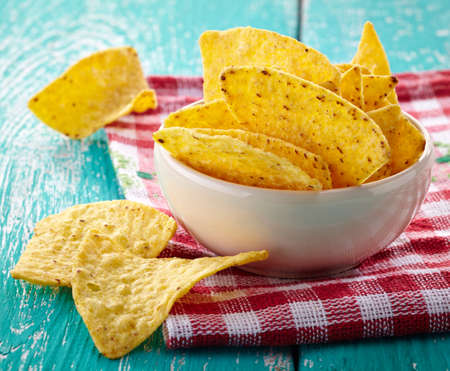 corn chip: Bowl of nachos on blue wooden background Stock Photo