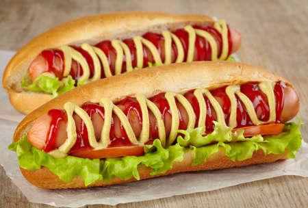 Twee hotdogs met sla en tomaat