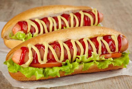 Two hot dogs with lettuce and tomato