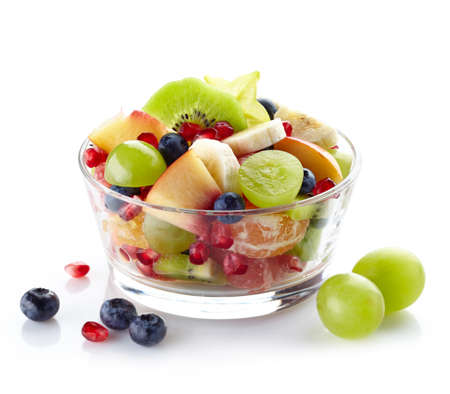 Bowl of healthy fresh fruit salad on white background