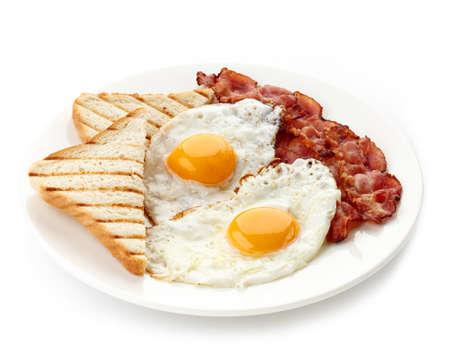 白で隔離されるトースト揚げ卵とベーコンの朝食の皿 写真素材