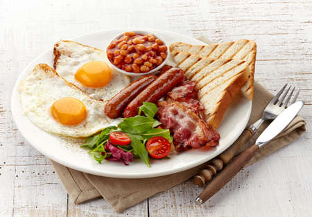 English breakfast with fried eggs, bacon, sausages, beans, toasts and fresh salad