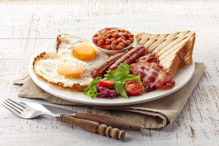 Englisches Frühstück mit Spiegeleiern, Speck, Würstchen, Bohnen, Toast und frischem Salat Standard-Bild - 24928233