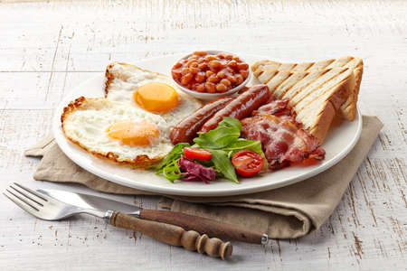 bacon baked beans: English breakfast with fried eggs, bacon, sausages, beans, toasts and fresh salad