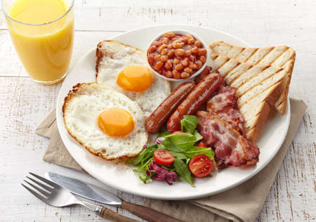 baked beans: English breakfast with fried eggs, bacon, sausages, beans, toasts and fresh salad