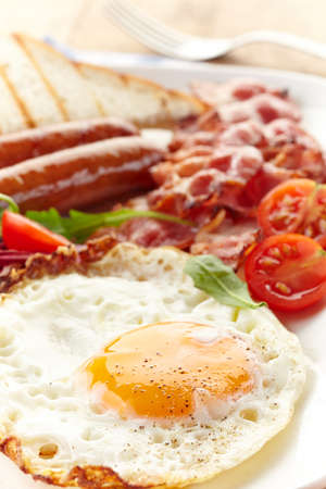 Engels ontbijt met gebakken eieren, spek, worstjes, bonen, toast en verse salade Stockfoto