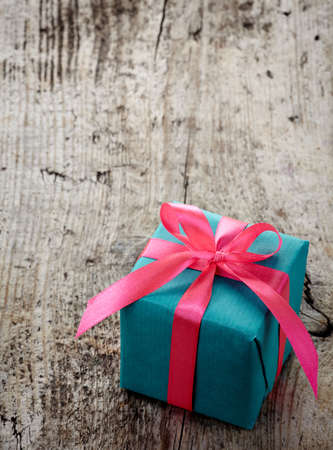blue gift box: Bright blue gift box with pink ribbon on wooden background