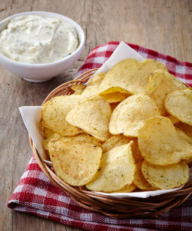 dips: Basket of potato chips and bowl of dip on wooden background