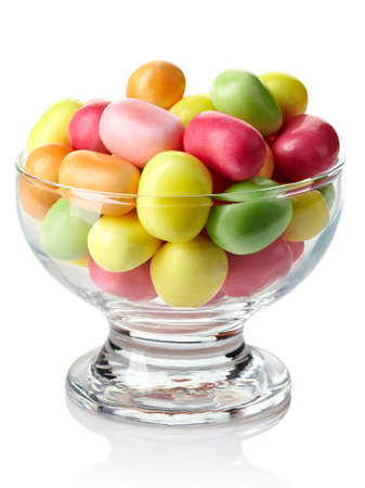 Bowl of colorful chewing candies isolated on white background photo