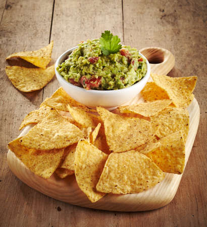 Guacamole dip and nachos on wooden background
