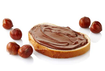 avellanas: Rebanada de pan con crema de chocolate y avellanas aislados en blanco