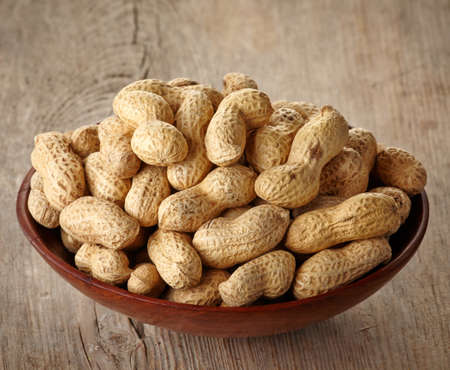 unpeeled: Bowl of peanuts on wooden  Stock Photo