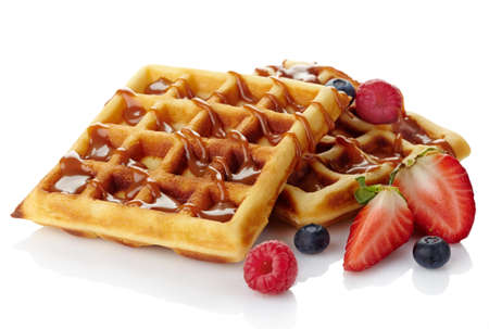 Belgium waffles with caramel sauce and fresh berries isolated on white