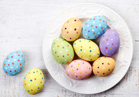 Plate of colorful Easter eggs on white wooden background photo