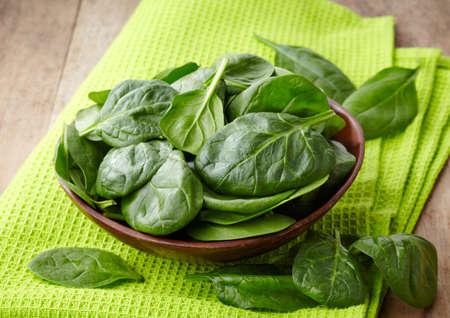 espinacas: Tazón de hojas de espinaca fresca sobre fondo de madera