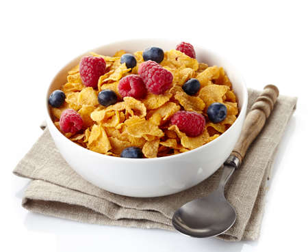 Bowl of corn flakes and fresh berries isolated on white background photo