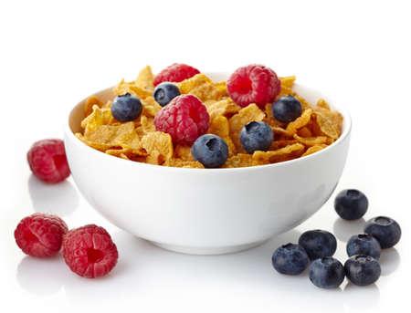 cereal: Tazón de copos de maíz y bayas frescas aisladas sobre fondo blanco