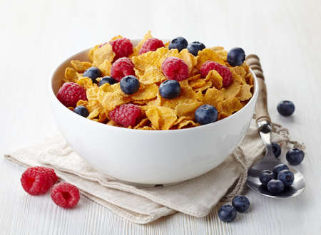 corn flakes: Bowl of corn flakes and fresh berries on white wooden background Stock Photo
