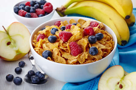 Bowl of corn flakes and fresh berries and fresh fruits photo