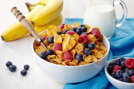 corn flakes: Bowl of corn flakes and fresh berries, jug of milk and bananas Stock Photo