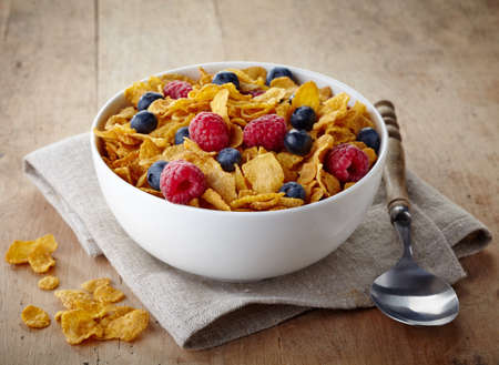 Bowl of corn flakes and fresh berries on wooden background photo