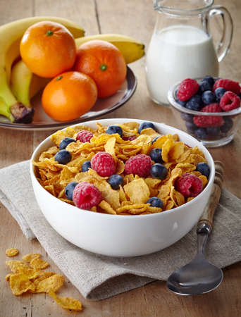 corn flakes: Bowl of corn flakes and fresh berries, jug of milk and fresh fruits on wooden background