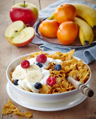 corn flakes: Bowl of corn flakes and fresh berries  and fruits on wooden background