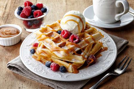 Piatto di waffle belgi con gelato, salsa al caramello e frutti di bosco freschi