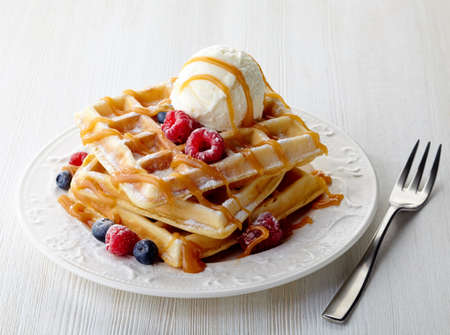 Plate of belgium waffles with ice cream, caramel sauce and fresh berries