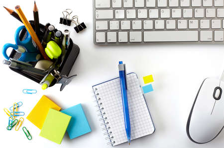 Office desktop with keyboard, mouse, notebook and basket of writing tools Stock Photo