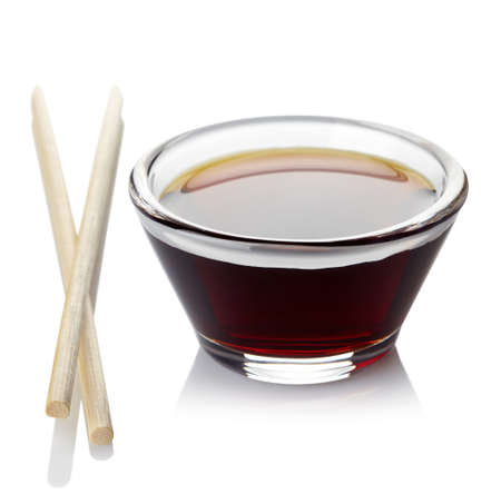 Bowl of soy sauce and two chopsticks isolated on white background Stock Photo